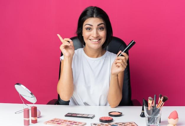 미소 짓는 아름다운 여성은 파우더 브러시 포인트를 위로 들고 있는 메이크업 도구를 들고 테이블에 앉아 있다