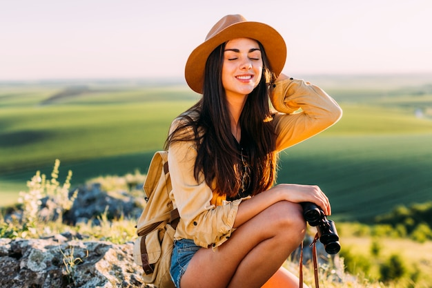 Улыбаясь красивая женщина, сидя на камне, холдинг бинокль