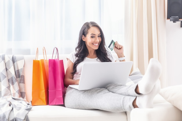 Smiling beautiful woman sitting on a sofa in her flat with feet up, doing online shopping on a laptop with a payment card in her hand and pink and orange paper shopping bags next to her.