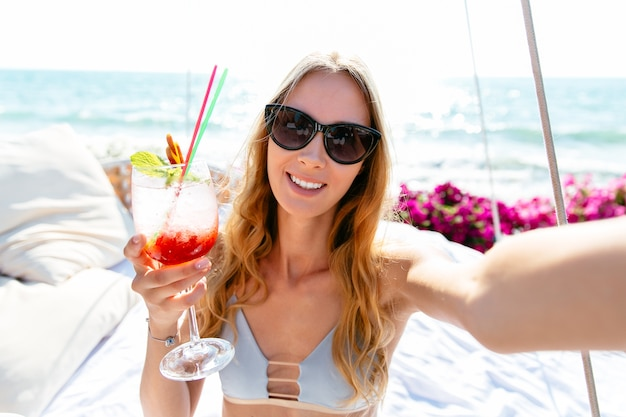 Smiling beautiful woman in swimsuit and sunglasses, holding a glass of cold cocktail.