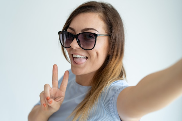 Smiling beautiful woman taking selfie photo, showing victory sign and looking at camera.