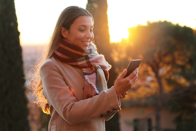 屋外のスマートフォンを使用して笑顔の美しい女性