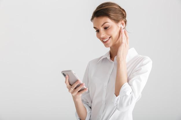 흰색 배경 위에 격리된 무선 이어폰과 휴대 전화를 사용하여 웃는 아름다운 여성