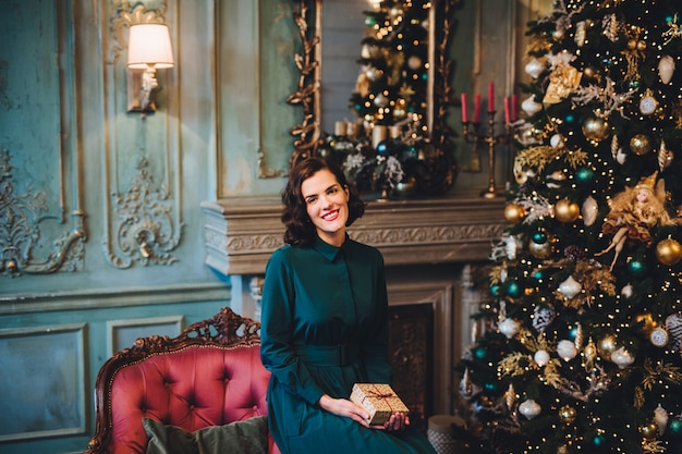 Smiling beautiful woman wears nice dress, sits near christmas tree in room, holds present
