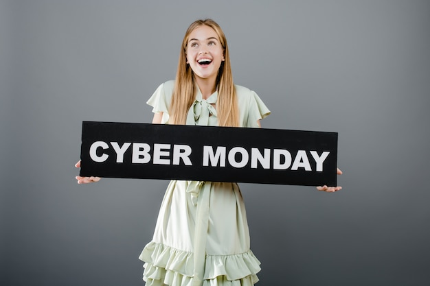 Smiling beautiful woman with cyber monday sign isolated over grey