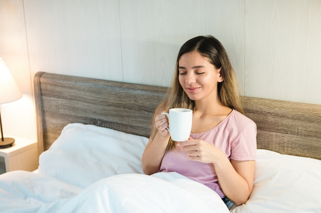 Smiling beautiful woman with eyes closed holding a cup while lying in bed with white bedding