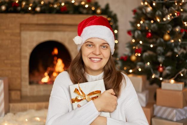 クリスマスツリーと暖炉のある屋内でポーズをとってギフトボックスと美しい女性の笑顔