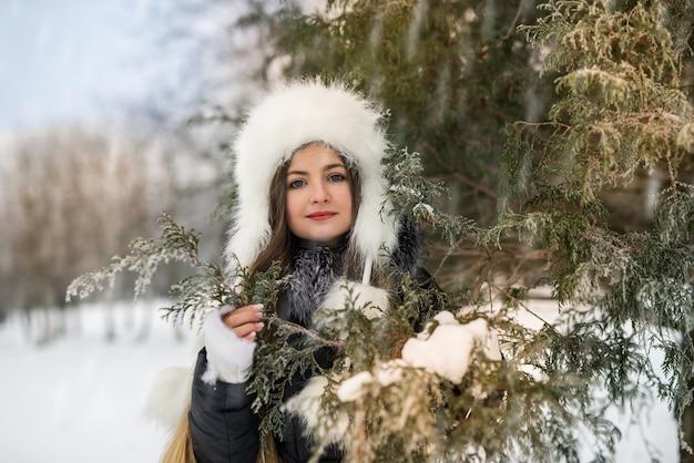 Улыбающаяся красивая женщина с ветвями деревьев в зимнем парке