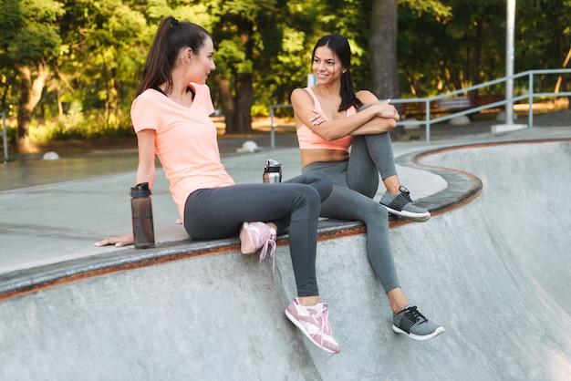 앉아서 콘크리트 운동장에 물병으로 이야기하는 운동복에 아름다운 여성 미소 짓기