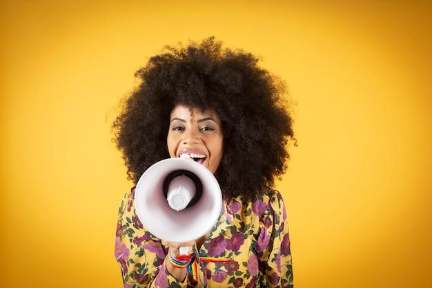 노란색 배경 위에 확성기로 비명 곱슬 아프로 머리를 가진 아름 다운 젊은 아프리카 계 미국인 여자를 웃 고.