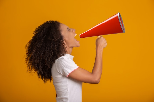 Smiling beautiful young african american woman with curly afro hair screaming by megaphone over yellow wall