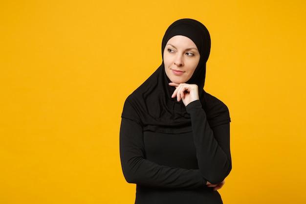 黄色の壁、肖像画に分離されたヒジャーブの黒い服を着て美しい若いアラビアのイスラム教徒の女性の笑顔。人々の宗教的なライフスタイルの概念。