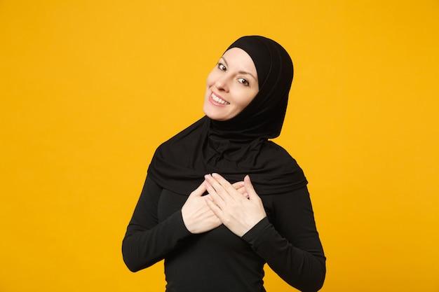 ヒジャーブの黒い服を着て笑顔の美しい若いアラビアのイスラム教徒の女性は、黄色の壁の肖像画に分離された心に手を置きます。人々の宗教的なイスラムのライフスタイルの概念。