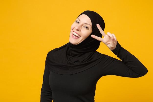 黄色の壁の肖像画に分離された勝利のサインを示すヒジャーブの黒い服を着た美しい若いアラビアのイスラム教徒の女性の笑顔。人々の宗教的なイスラムのライフスタイルの概念。