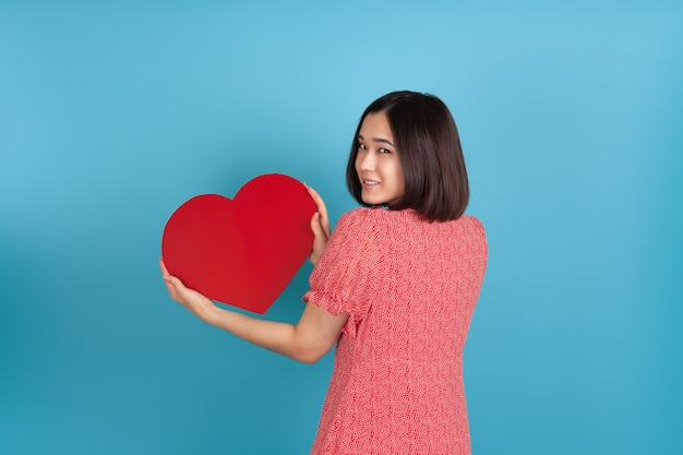 Smiling beautiful young asian woman in red dress stands back and holds big red paper heart