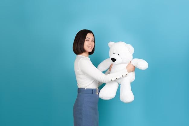 웃는 아름 다운 젊은 아시아 여자 옆으로 서 있고 큰 흰색 곰을 보유