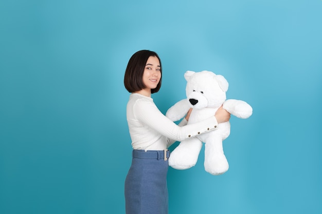 Smiling beautiful young asian woman stands sideways and holds a large white teddy bear