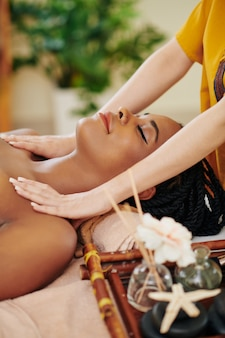 Smiling beautiful young black woman enjoying relaxing face, head and shoulders massage in spa salon