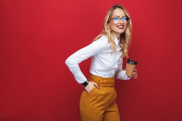 테이크 아웃 커피 컵을 들고 빨간색 배경 위에 고립 된 서 웃는 아름 다운 젊은 금발의 여자