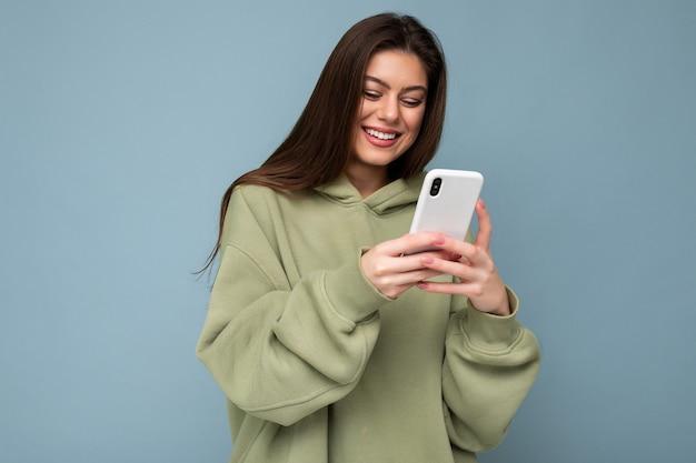 Улыбается красивая молодая брюнетка женщина в стильной зеленой толстовке с капюшоном с помощью мобильного телефона