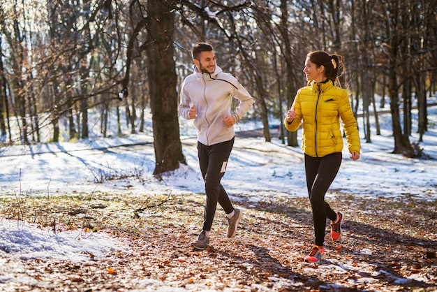 Smiling beautiful young flirting couple jogging in sportswear through the forest in the sunny winter morning.
