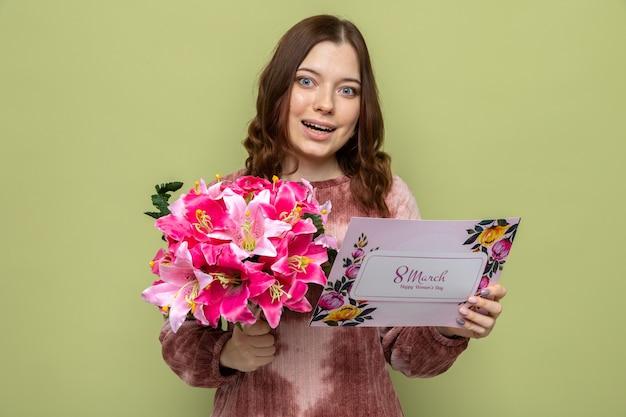 Bella ragazza sorridente il giorno delle donne felici che tiene il mazzo con la cartolina d'auguri