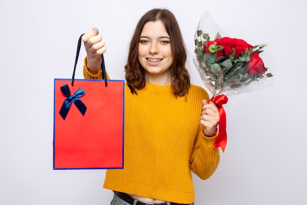 Smiling beautiful young girl holding gift bag with bouquet