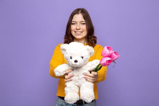 Улыбающаяся красивая молодая девушка протягивает цветы с плюшевым мишкой