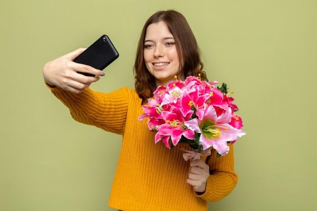 행복한 여성의 날에 웃고 있는 아름다운 소녀가 꽃다발을 들고 올리브 녹색 벽에 고립된 셀카를 찍습니다