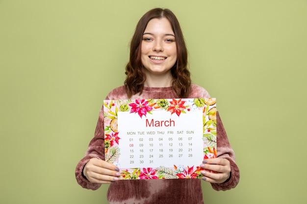 행복한 여성의 날에 웃고 있는 아름다운 어린 소녀가 올리브 녹색 벽에 격리된 카메라에서 달력을 들고 있다
