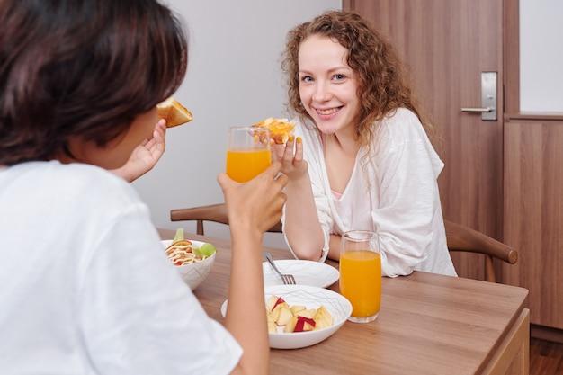朝食にピザとオレンジジュースを楽しむ美しい若いレズビアンのカップルの笑顔