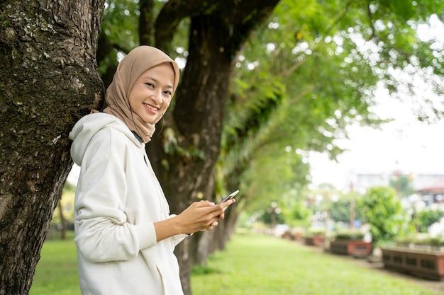 屋外での運動休憩中に携帯電話を使用して美しい若いイスラム教徒の女性の笑顔