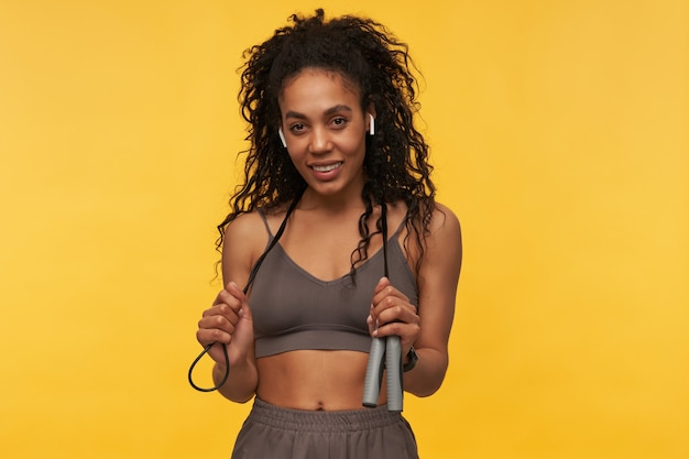 Smiling beautiful young woman athlete with wireless earphones standing and holding skipping rope on neck isolated over yellow wall