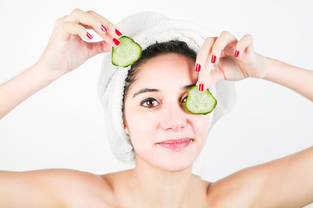 Smiling beautiful young woman covering eyes with cucumber slice against white background