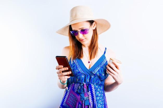 흰색 바탕에 휴가에 스마트폰으로 여름 해변 문자 메시지를 위해 옷을 입고 웃고 있는 아름다운 젊은 여성