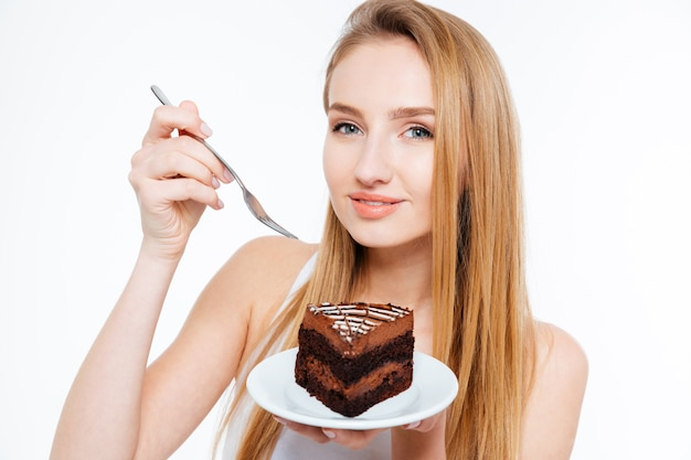 흰색 배경 위에 초콜릿 케이크를 먹고 웃는 아름다운 젊은 여자