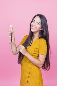 Smiling beautiful young woman holding champagne flute against pink background