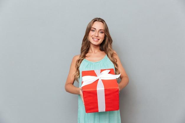Улыбается красивая молодая женщина, держащая подарочную коробку