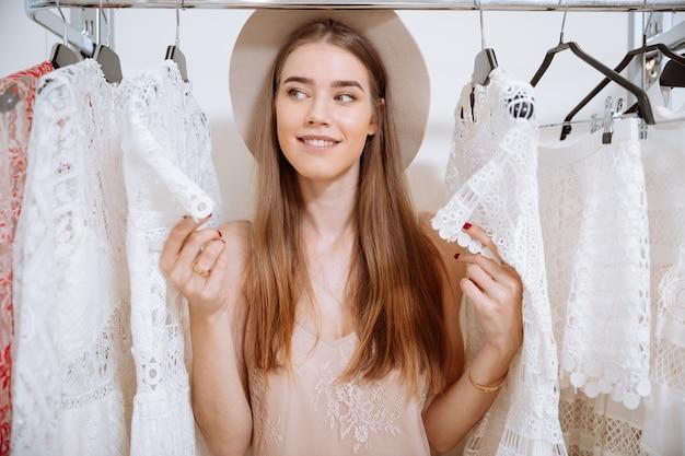 衣料品店に立っている帽子の美しい若い女性の笑顔