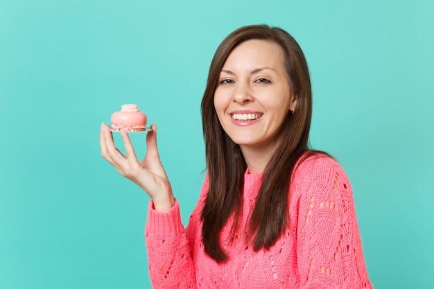 Улыбается красивая молодая женщина в вязаном розовом свитере, держа в руке торт, изолированные на синем фоне бирюзовой стены, студийный портрет. люди искренние эмоции, концепция образа жизни. копируйте пространство для копирования.