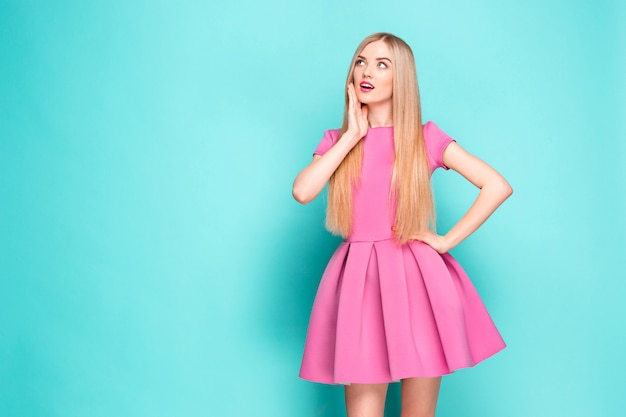 핑크 미니 드레스 포즈, 뭔가 제시 하 고 멀리보고 웃는 아름 다운 젊은 여자.