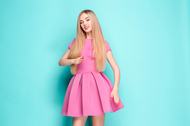 Улыбка красивая молодая женщина в розовом мини-платье позирует, представляя что-то и глядя.
