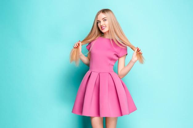 핑크 미니 드레스 포즈에서 웃는 아름 다운 젊은 여자