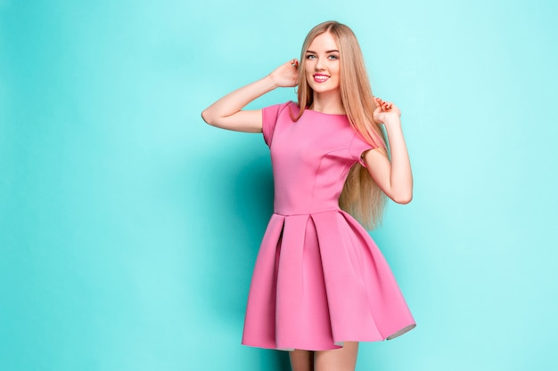 Smiling beautiful young woman in pink mini dress posing at studio