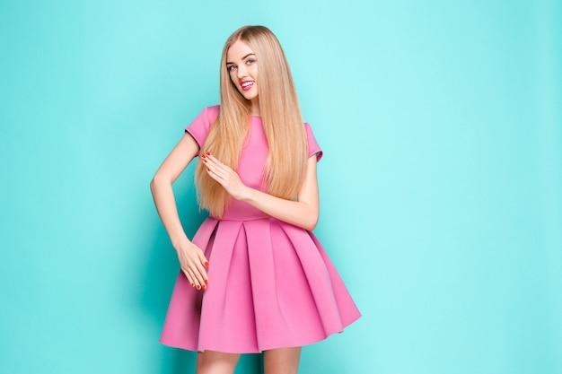 Smiling beautiful young woman in pink mini dress posing