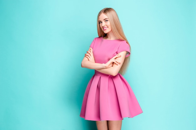 Smiling beautiful young woman in pink mini dress posing