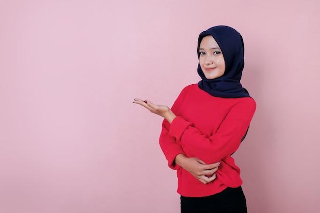 Улыбающаяся красивая молодая женщина показывает что-то в красной футболке