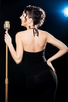 Smiling beautiful young woman singer holding golden vintage microphone in spotlight
