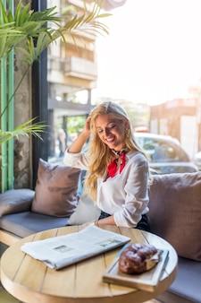 焼きたてのパンをテーブルの上のレストランに座っている笑顔の美しい若い女性