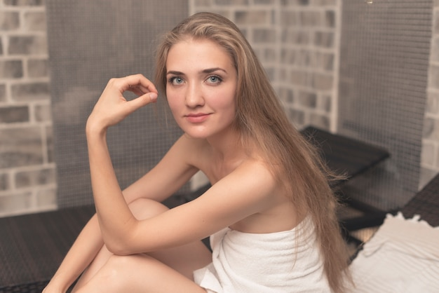Smiling beautiful young woman sitting on lounge chair in spa
